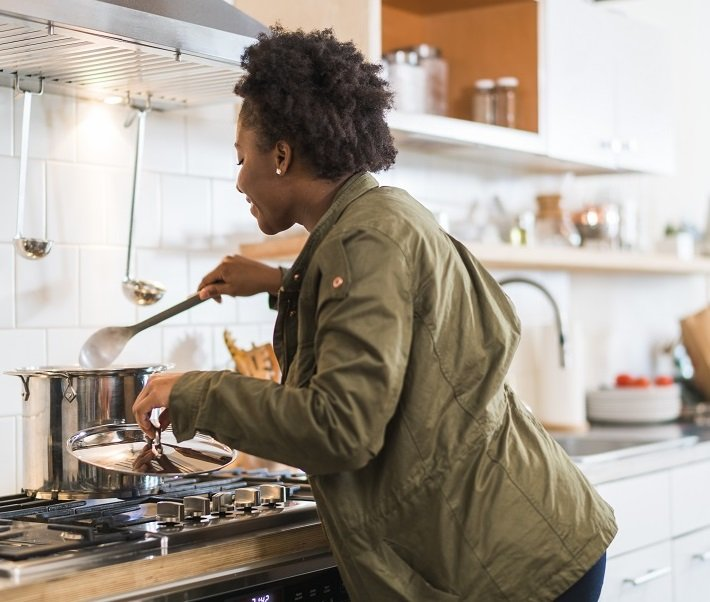 An afro-american girl cooking a soup